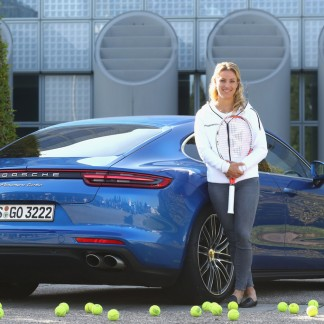 Angie poses in front of a new Porsche Panamera Turbo after returning as new Tennis World number One and winner of the US Open at Munich Airport // Getty Images